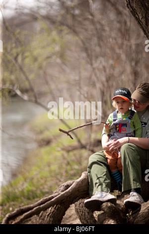 Jeune garçon tenant un bâton et assis sur les genoux de sa mère. Banque D'Images