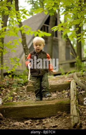 Jeune garçon escalade dans les escaliers dans les bois, la réalisation d'un bâton. Banque D'Images