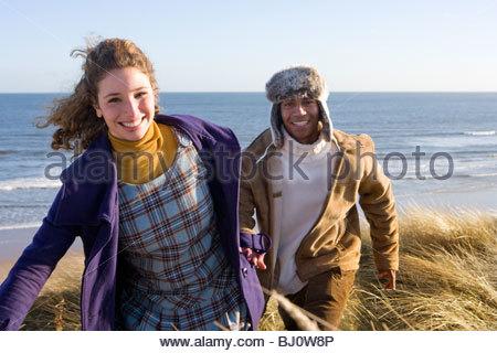 Couple walking on sand dune près de ocean Banque D'Images