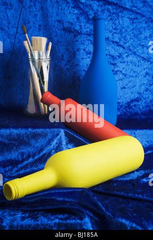 Bouteilles dans des couleurs primaires avec des pinceaux. Banque D'Images