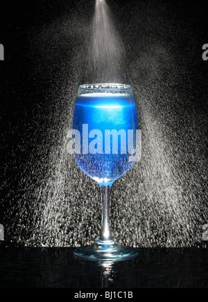 En verre bleu avec de l'eau glacée en mouvement Banque D'Images