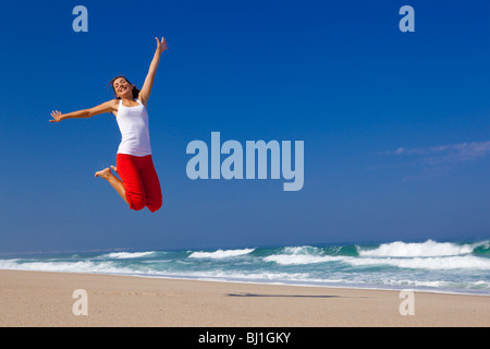 Belle jeune femme sautant sur la plage Banque D'Images