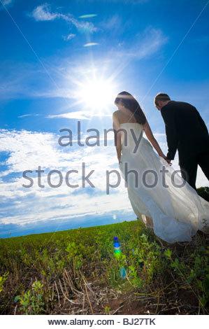 Mariée et le marié marche sur une pelouse Banque D'Images