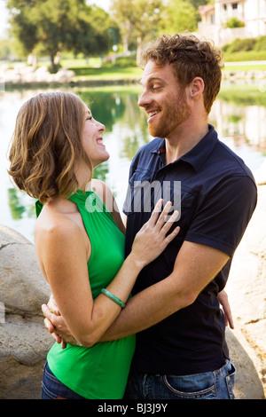 Fun loving attrayante jeune couple joyeux joyeusement en se tenant ensemble 30s'il y à d'autres à chaque parc au Banque D'Images