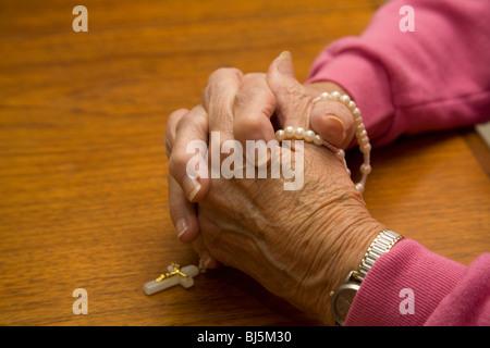 Priant mains d'une femme senior avec chapelet Banque D'Images