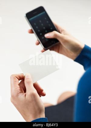 Businesswoman holding blank business card et composer les numéros de téléphone mobile Banque D'Images