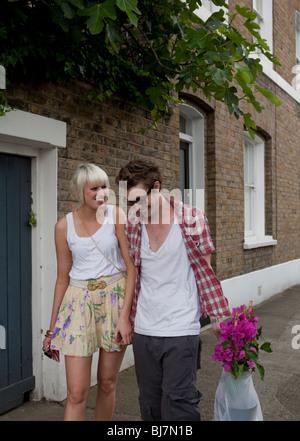 Couple walking home de marché aux fleurs un dimanche après-midi en été, Londres, UK, Angleterre, Europe Banque D'Images