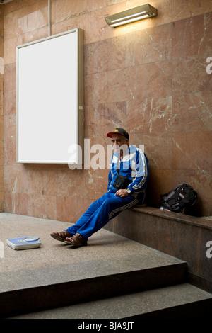 Man location échelle sur l'escalier de marbre avec blank billboard dans l'arrière-plan Banque D'Images