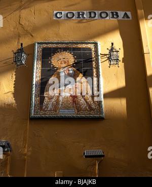 Streetsign à Cordoba et sol carrelé photo d'icône religieuse sur mur jaune en espagne Banque D'Images