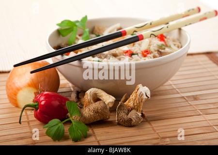 Plat de nouilles ramen végétarien, baguettes au repos sur la cuvette, les ingrédients en premier plan Banque D'Images