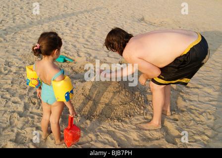 Cute Girl touristiques avec son père la construction d'un palais de nice en sable de mer.père et fille jouer à Kovalam Banque D'Images