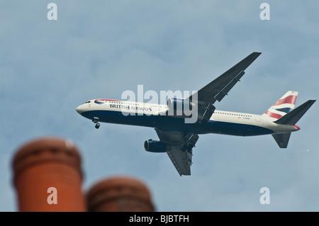 British Airways avion volant à basse altitude au-dessus des maisons à proximité de l'aéroport de Heathrow. Banque D'Images