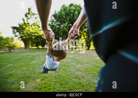 Père spinning petit garçon dans parc, cropped Banque D'Images