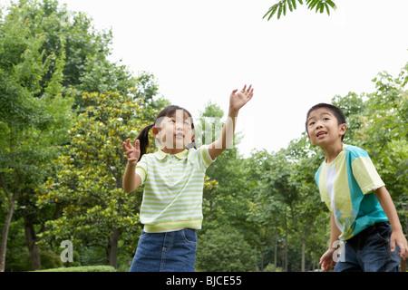 Jeune garçon et fille s'amusant dans le parc Banque D'Images