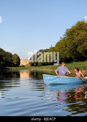 Jeune couple en bateau à rames en face de l'Herren château sur le lac de Chiem, Chiemgau Haute-bavière Allemagne
