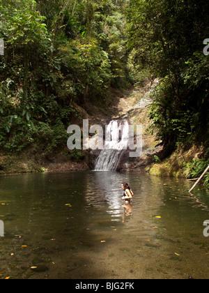 Baignade en rivière près de fille cascade situé dans la forêt tropicale des Caraïbes Tobago de plantes tropicales Banque D'Images