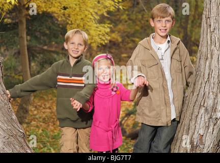Trois enfants se tenant la main entre l'automne arbres en automne Banque D'Images