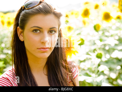 Close up of young jolie femme dans un champ de tournesol Banque D'Images