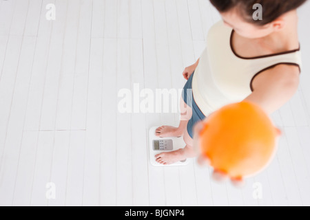 Femme tenant une orange et la pesée elle-même sur un pèse-personne Banque D'Images