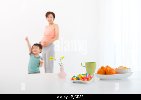 Femme enceinte et son fils d'âge préscolaire debout dans salle à manger avec des bonbons et des fruits sur la table Banque D'Images