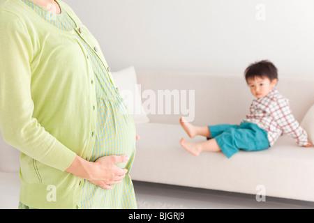 Portrait de femme enceinte dans la salle de séjour avec l'âge préscolaire fils assis sur le canapé à l'arrière-plan Banque D'Images