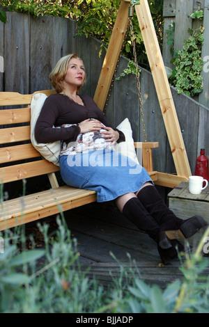 Femme enceinte dans le jardin arrière looking up, troisième trimestre de la grossesse Banque D'Images