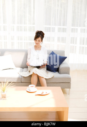 Woman Reading magazine on sofa in living room