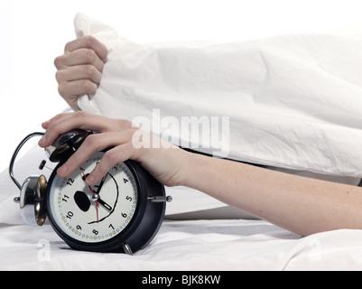 Jeune femme femme au lit l'éveil fatigué maintenant réveil sur fond blanc Banque D'Images