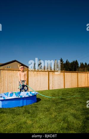Garçon en maillot de bain avec palmes et tuba dans une cour Banque D'Images