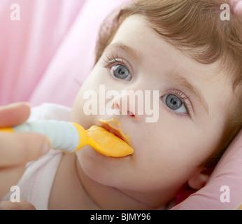 Nourrir bébé mère cuillère jaune fond blanc Banque D'Images