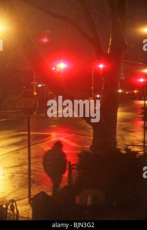Lonely man walking down street dans la pluie de nuit Banque D'Images