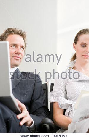 Un homme et une femme en attente dans un aéroport Banque D'Images