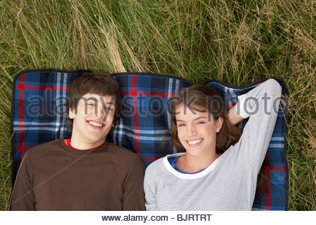 Young couple relaxing in a field Banque D'Images