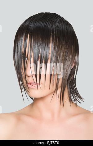 Une femme avec des cheveux humides couvrant son visage Banque D'Images