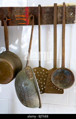 Ancienne cuisine casseroles accroché au mur en Italie Banque D'Images