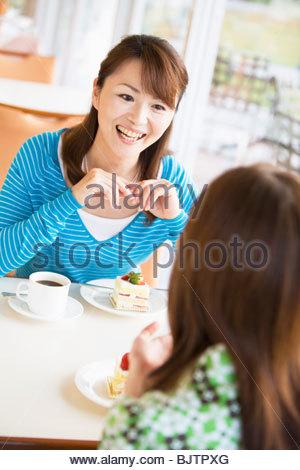 Deux femmes manger un gâteau au café un Banque D'Images