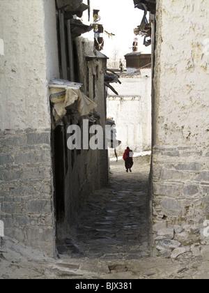 Un moine bouddhiste s'exécute dans l'allée entre les deux bâtiments à l'Drepung à Lhassa, Tibet Banque D'Images