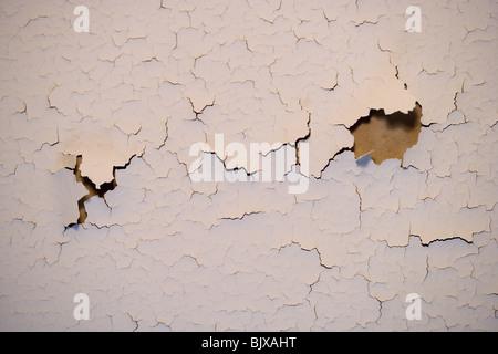 Fissures de la peinture sur un mur intérieur d'une maison. Banque D'Images