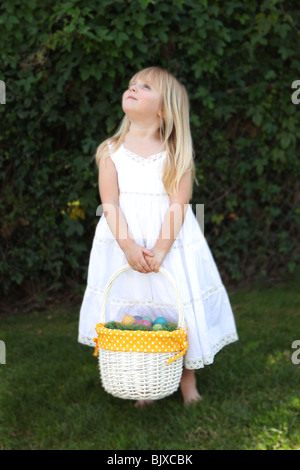 Sweet Little Girl Holding Easter basket avec des oeufs dans une robe en dentelle blanche Banque D'Images