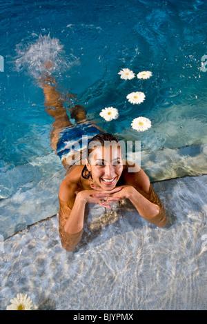 Portrait of mid-adult woman in pool avec des fleurs blanches Banque D'Images