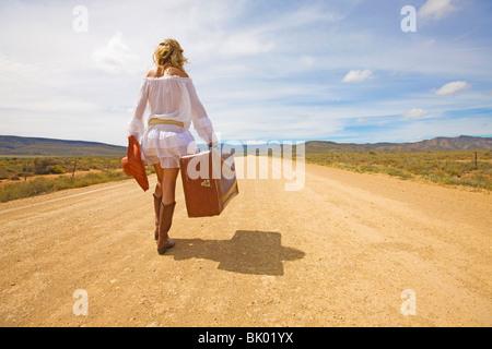 Femme seule sur la route du désert Banque D'Images