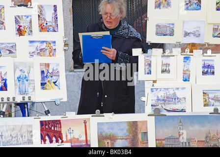 Une femme vente de peintures pour les touristes à Venise, Italie Banque D'Images