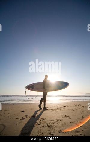 Jeune femme marchant sur une plage de surf avec surf Banque D'Images