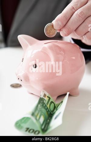 Mettre la main pièce dans piggy bank Banque D'Images
