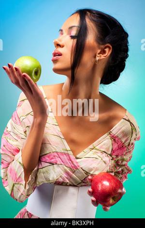 Jeune femme avec deux pommes. Riche des couleurs vives. Banque D'Images
