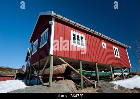 En bois rouge traditionnelle Rorbu cabane de pêcheur avec les bateaux de pêche enregistrés ci-dessous dans le village Banque D'Images