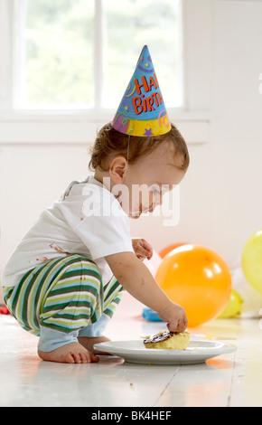 Boy eating cake sur son premier anniversaire Banque D'Images