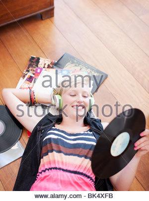 Woman listening to headphones plancher et la tenue de dossier de musique Banque D'Images