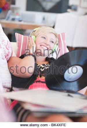 Woman laying on sofa listening to headphones holding et l'enregistrement de la musique Banque D'Images