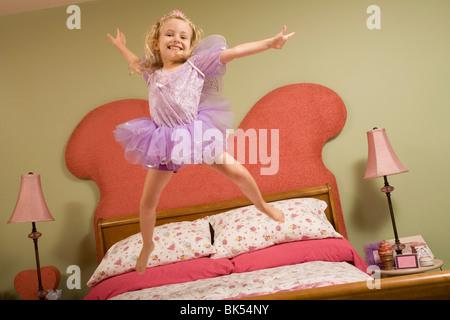 Petite Fille habillée en Fée Jumping on Bed Banque D'Images